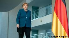 Angela Merkel walks up to a podium (AFP/M. Kappeler)