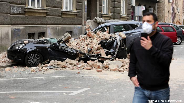 Muškaac s maskom na licu ide pored automobila na koje se urušio dio zgrade u Zagrebu