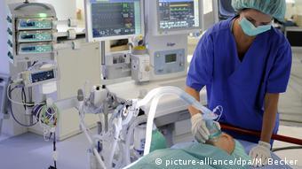 Paciente usando ventilador para respirar, aplicado por enfermeira em sala de cirurgia