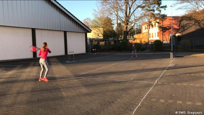 Djeca igraju tenis na parkiralištu