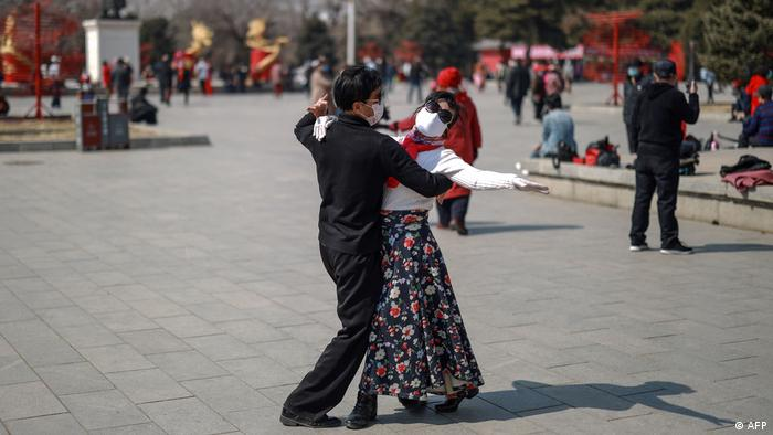 Casal dançando com máscara respiratória na rua na China