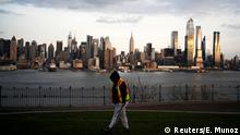 The Empire State Building and the skyline of New York are seen while a man walks around a local park in Weehawken, New Jersey, as the coronavirus disease (COVID-19) outbreak continues in New York, U.S., March 22, 2020. REUTERS/Eduardo Munoz TPX IMAGES OF THE DAY