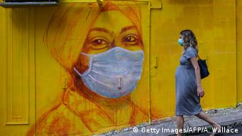 Mundschutz-Graffiti und Frau mit Maske in Hongkong (Bild: Getty Images/AFP/A. Wallace)