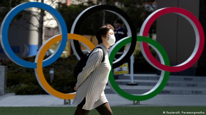 A woman in a mask walks past the Olympic rings in Tokyo. File photo: March 13, 2020.