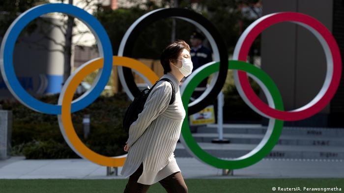 Una persona enmascarada camina frente al símbolo de los Juegos Olímpicos.