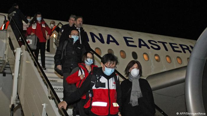 Chinese aid workers walk off a plane in Italy