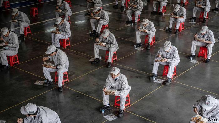 Funcionários sentam longe durante a pausa em fábrica da Honda em Wuhan