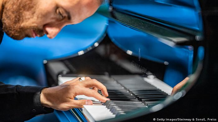Igor Levit bows closely to the piano keyboard, ringed finger playing notes