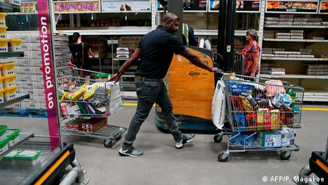 A man pulling two shopping carts (AFP/P. Magakoe)