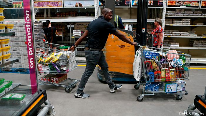 A man pulling two shopping carts
