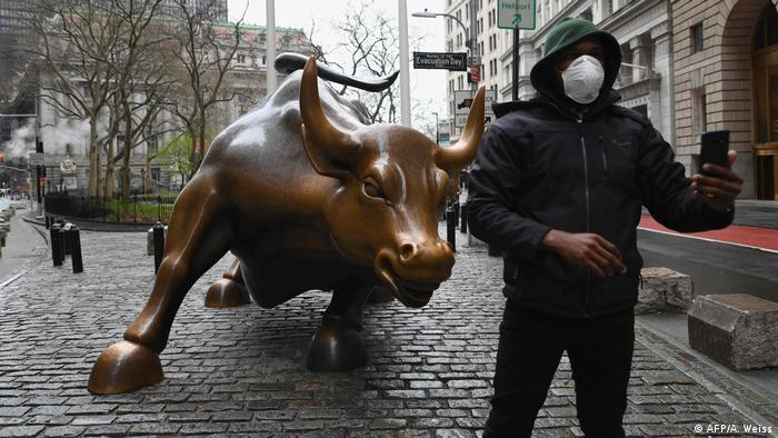 A man wearing a face mask takes a selfie at the Charging Bull statue near the New Stock Exchange