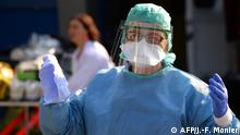 TOPSHOT - A nurse anesthetist gestures during the disinfection of ambulances which carried six coronavirus patients at the Brest hospital, evacuated by air from the French eastern city of Mulhouse, in Brest, western France, on March 24, 2020, on the eight day of a lockdown aimed at curbing the spread of the COVID-19 (novel coronavirus) in France. (Photo by JEAN-FRANCOIS MONIER / AFP)