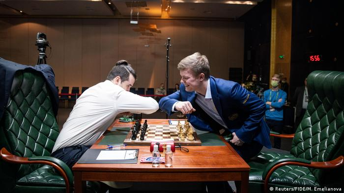 Zwei Schachspieler begrüßen sich über dem Schachbrett mit den Ellbogen.