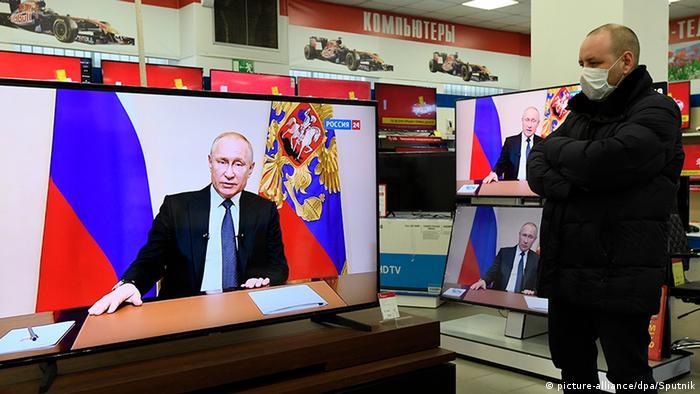 Мужчина в маске смотрит выступление Путина о коронавирусе по телевизору