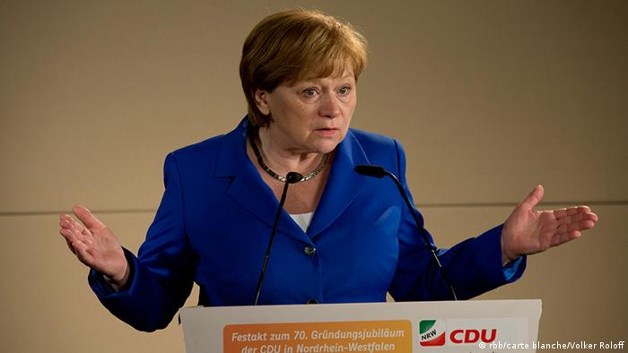 Film still Die Getriebenen: A woman stands at a lectern, arms outstretched, apparently holding a speech