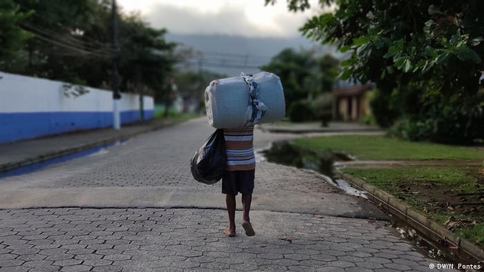 Homem de costas carrega saco