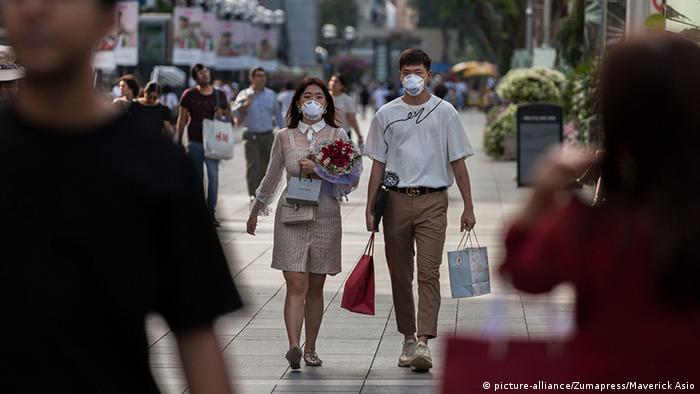 A couple wearing protective masks walk along Orchard Road in Singapore