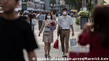 February 14, 2020, Singapore, Singapore: A couple wearing protective face masks walk along Orchard Road, a famous shopping district in Singapore, on Valentine's Day..Singapore declared the COVID-19 outbreak as Code Orange on February 7, 2020. (Credit Image: © Maverick Asio/SOPA Images via ZUMA Wire |