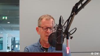 Radiosprecher liest im Studio die Nachrichten vor.