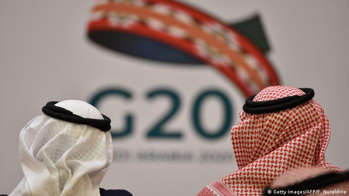 Unidentified guests attend a meeting of Finance ministers and central bank governors of the G20 nations in the Saudi capital, Riyadh, next to a G20 sign
