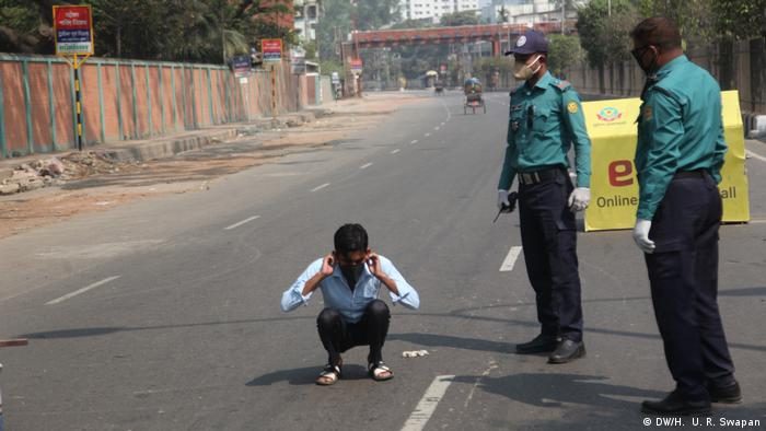 Police and a detained man in Dhaka, Bangladesh (DW/H. U. R. Swapan)