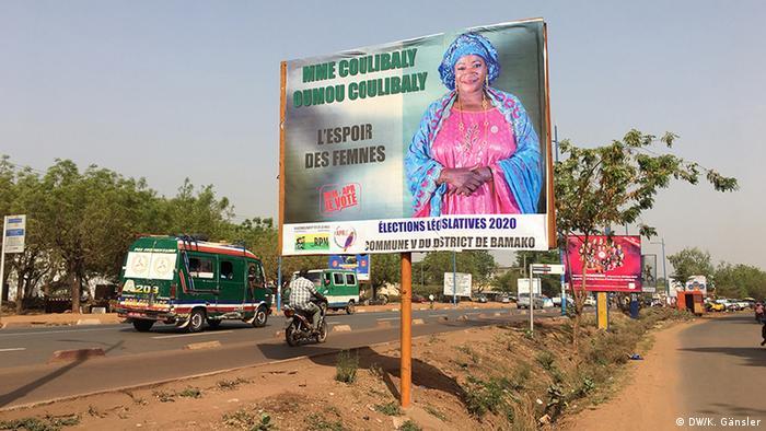 An election campagin board by a busy road in Mali