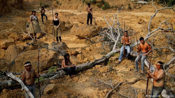 A group of men, boys and girls stand in the dust of a once forested area of the Amazon