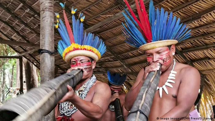 Dois indígenas de cocar sopram um instrumento tradicional