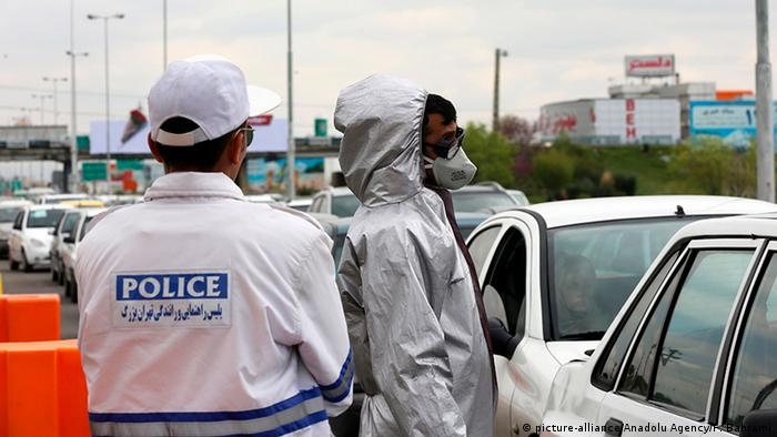 Officials check body temperatures in a line of cars in Tehran