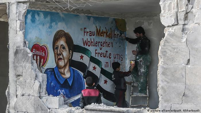 Em ruínas de Binnish, na Síria, pintor homenageou Merkel em março