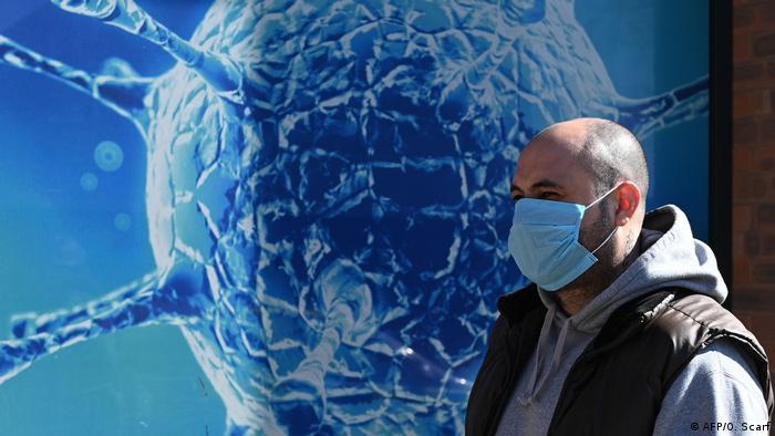 Un bărbat cu mască trece pe lângă o imagine a noului coronavirus