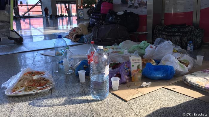 Бутылки с водой и еда в одноразовой посуде на полу в аэропорту Внуково