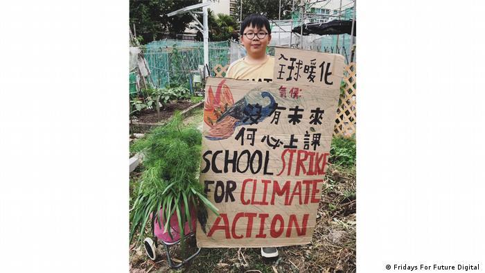 Lance Lau präsentiert sein Protestplakat im Garten des Nachbarn