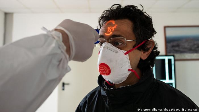 Медик измеряет температуру пациенту бесконтактным градусником
