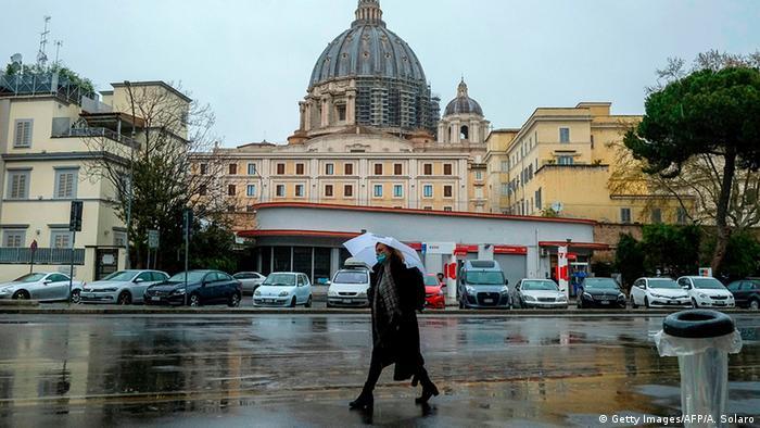 A woman wearing a face mask walks across a street in Rome