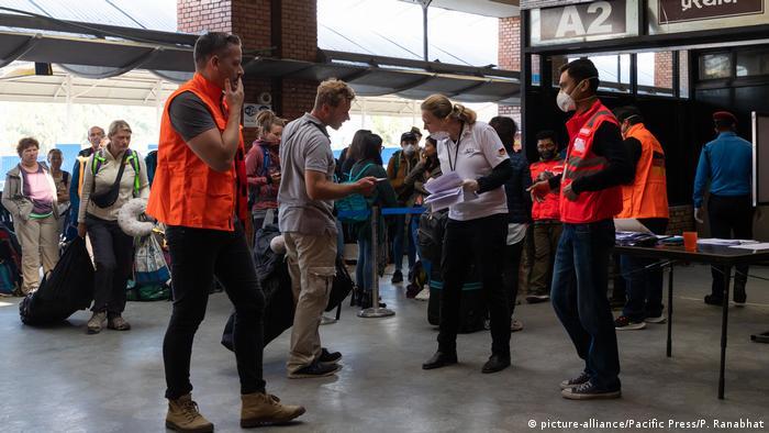German embassy staff check German tourists at an airport in Kathmandu, Nepal