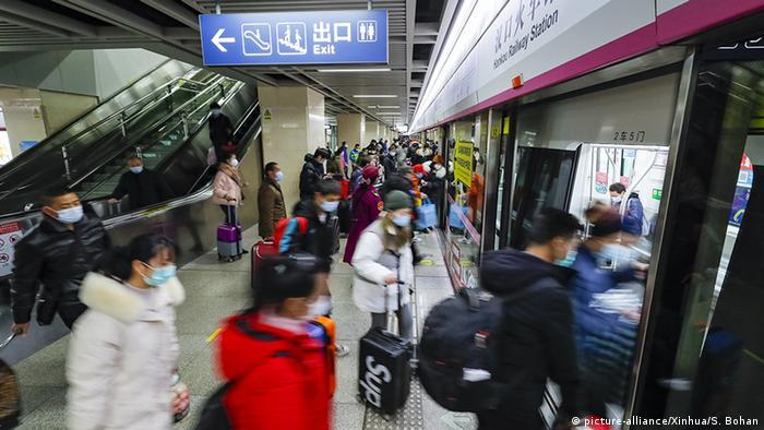 Pessoas usando máscaras entram no metrô em Wuhan