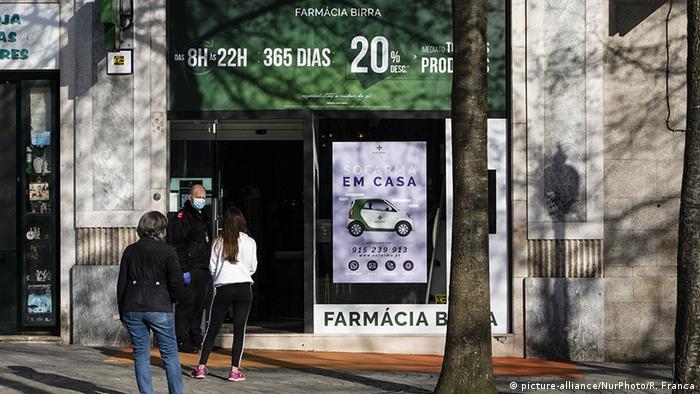Pessoas esperam em fila de farmácia no Porto, em Portugal