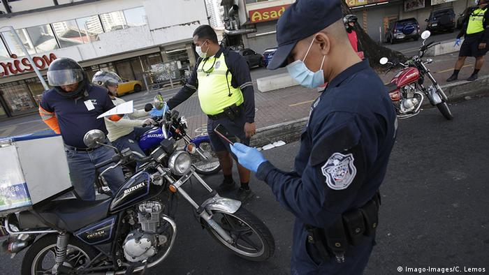 Members of the police work at a checkpoint to verify the work permits of citizens