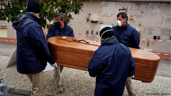 Employees of a mortuary carry the coffin of a person who died from the coronavirus disease