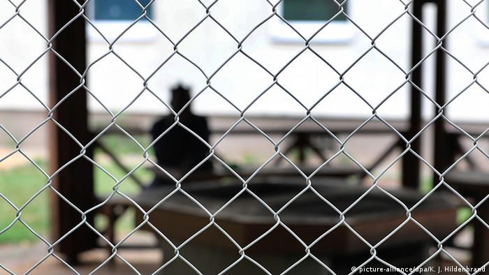 A person sits behind a chained link fence in a refugee center
