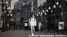 A man walks down a Moscow street wearing a face mask