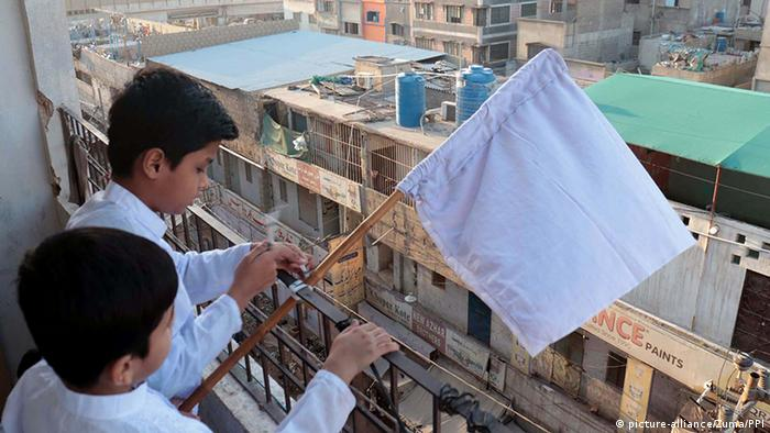 Two boys wave a white flag on a balcony in Pakistan (picture-alliance/Zuma/PPI)