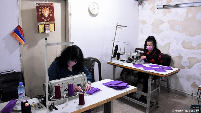 Two women in masks sewing more masks in Aleppo (Getty Images/AFP)