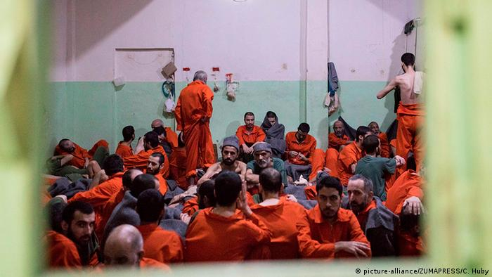 Men wearing orange jumpsuits crowded together in a room, sitting on the floor