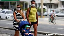 FILE PHOTO: A couple wearing protective face masks walk with their child along the Copacabana beach following the closure of the beaches amid the coronavirus disease (COVID-19) outbreak, in Rio de Janeiro, Brazil March 22, 2020. REUTERS/Pilar Olivares/File Photo