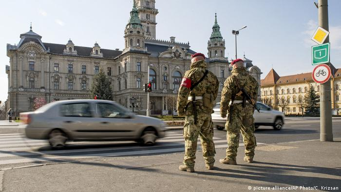 Military men stand on a street in Gyor, Hungary, as cars drive by