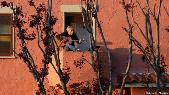Ein Mann sitzt mit seiner Gitarre am offenen Fenster und singt.