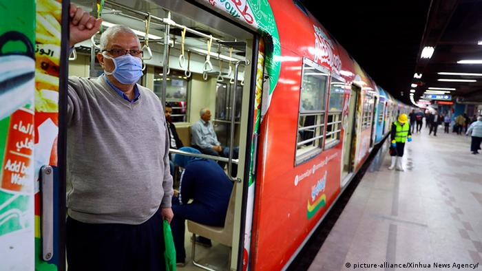 A passenger waits in the train as a man sprays disinfectant in a metro station in Cairo