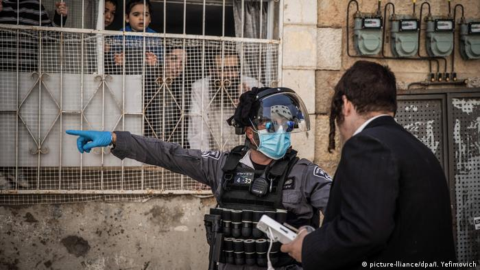 Israelischer Polizist mit Mundschutz und Handschuhen zeigt einem Mann den Weg (picture-lliance/dpa/I. Yefimovich)